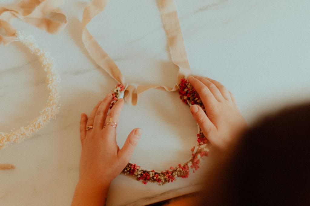 La créatrice en train de placer un ruban sur une couronne de fleurs